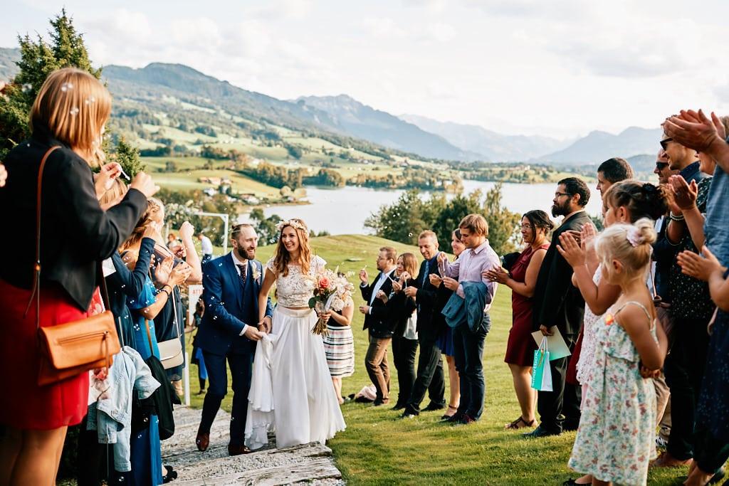 """Quand la cérémonie est en plein-air une haie d'invité est l'idéale pour célébrer la """"sortie"""" des mariés ! Ici au golf de Pont-La-Ville avec les pré-alpes fribourgeoise en arrière-plan ainsi que le lac de la Gruyère."""